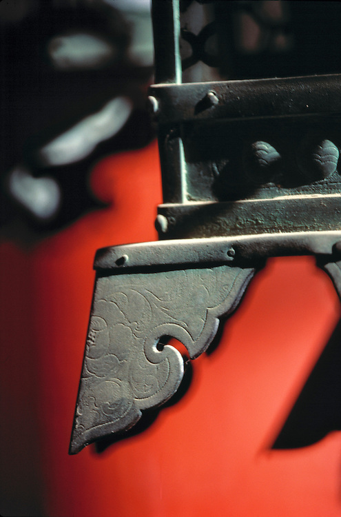 The carved detail of a metal lantern plays against a red background in the Kasuga Shrine, Nara, Japan.