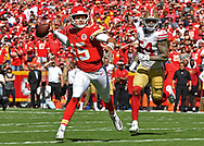 Quarterback Patrick Mahomes #15 of the Kansas City Chiefs throws a touchdown pass, scrambling away from defensive end Cassius Marsh #54 of the San Francisco 49ers during the first half at Arrowhead Stadium in Kansas City, Missouri.