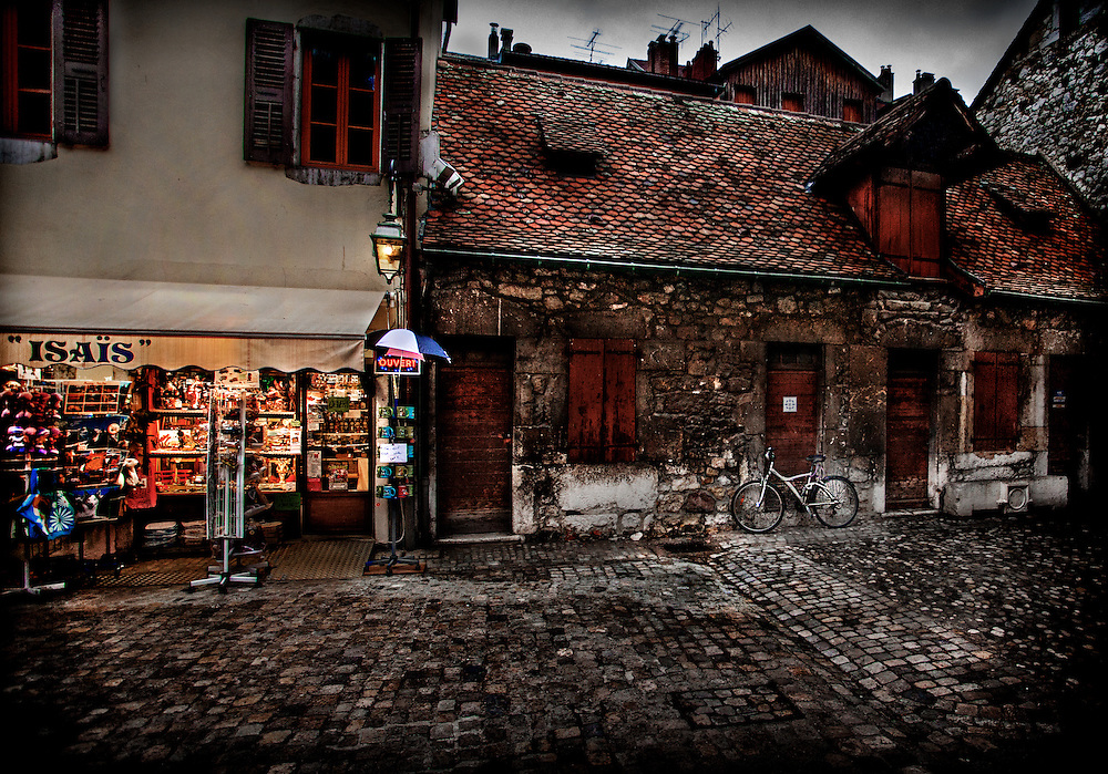 A bicycle leans against an old stone building outside a gift shop in Annecy, France.