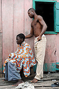 Benin March 1, 2008  An barber prepares to cut a customers hair with scissors and comb in hand.