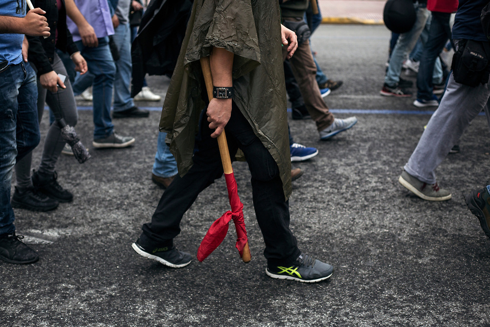 ATHENS, GREECE. May 17, 2017 - A man holds a red flag as he march towards the Greek Parliament during a 24 hour general strike against further austerity measures to be taken by the Greek Government.