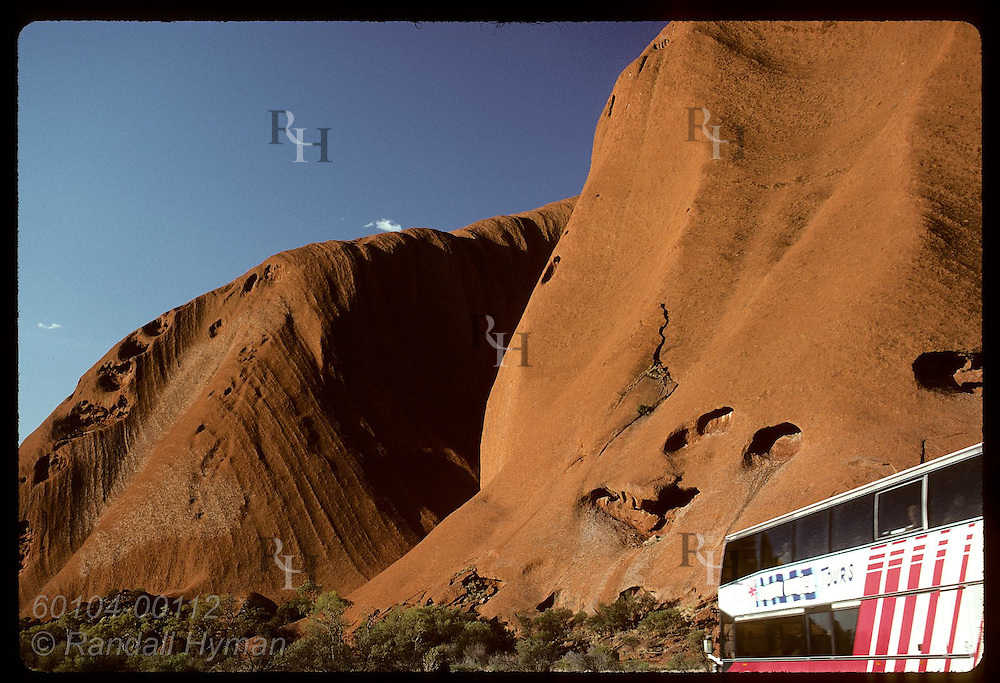 Tour bus drives along base of Ayers Rock on a summer afternoon at Uluru National Park. Australia