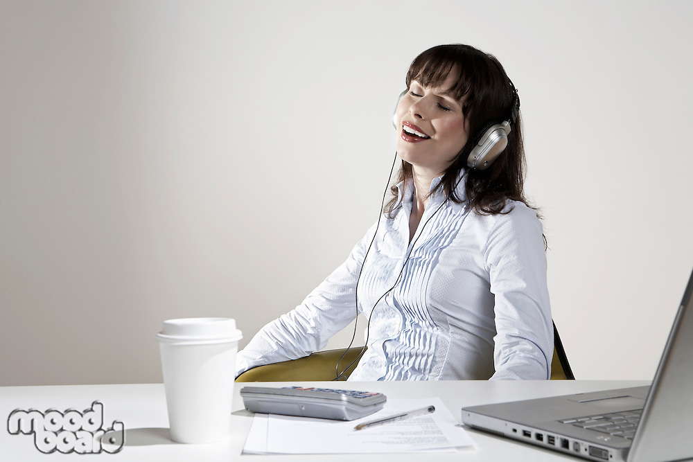Smiling woman with earphones relaxing at desk