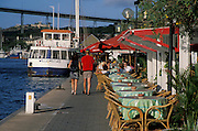Waterfront tables at Iguana Cafe in Punda, with ferry boat and Queen Juliana Bridge; Willemstad, Curacao, Netherlands Antilles.