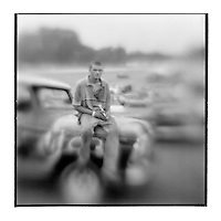 USA, Maryland, Mechanicsville, Blurred black and white image of young mechanic sitting on pickup truck hood in pits during Demolition Derby at Potomac Speedway