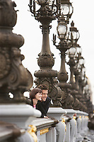 Couple looking over bridge through streetlights