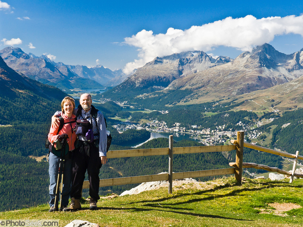 "Trekkers pose in a pasture on Muottas Muragl mountain with a view of Lake St. Moritz (Lej da San Murezzanor or St. Moritzer See), Lake Sils (Lej da Segl, famous for windsurfing), Lake Silvaplana (Lej da Silvaplauna), and Maloja mountain pass. Visit Graubünden canton and the Grison Alps, Switzerland, Europe. Reach Muottas Muragl by funicular railway from a train station between Samedan-St. Moritz and Pontresina on the Bernina Express line. The Swiss valley of Engadine translates as the ""garden of the En (or Inn) River"" (Engadin in German, Engiadina in Romansh, Engadina in Italian). For licensing options, please inquire."