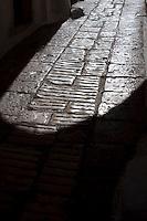 Un'ombra dell'arco di accesso alla Via Bixio Continelli nel borgo antico di Ostuni