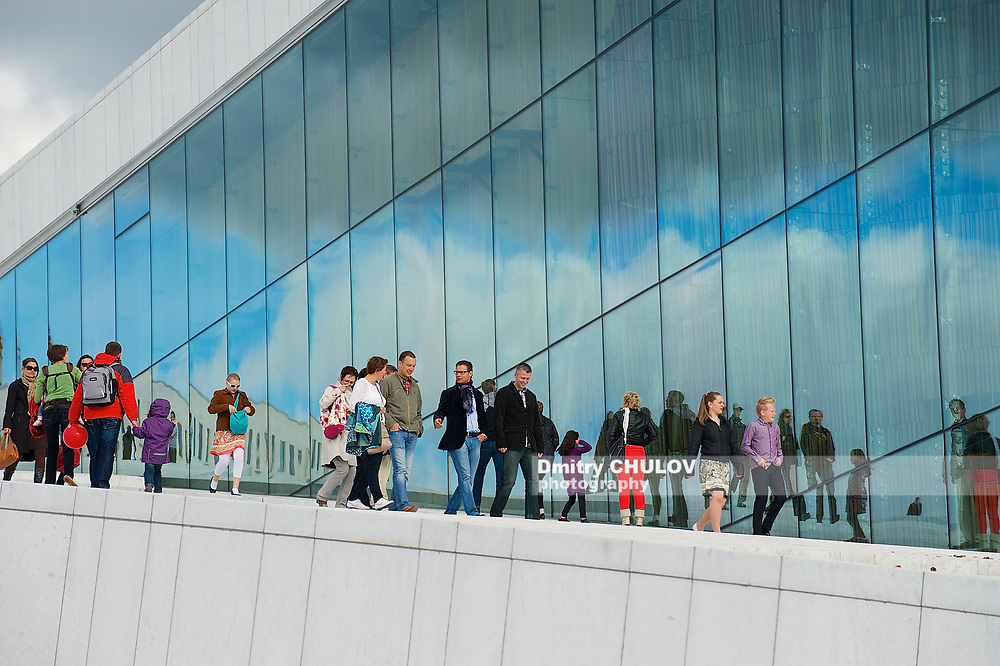 OSLO, NORWAY - JUNE 03, 2012: Unidentified people walk by the side wall of the National Oslo Opera House building in Oslo, Norway.
