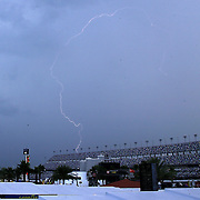 Lightning is seen outside of the Daytona International Speedway as bad weather moves into the are prior to the 57th Annual NASCAR Coke Zero 400 stock car race at Daytona International Speedway on Sunday, July 5, 2015 in Daytona Beach, Florida.  (AP Photo/Alex Menendez)