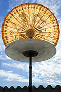 old style Asian paper umbrella on a round table against the sun