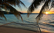 Hammock and palm trees on beach at sunset, Matangi Private Island Resort, Fiji.