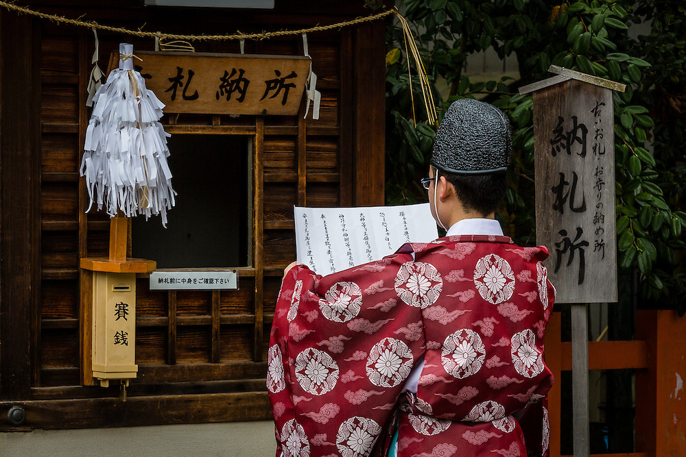 A shinto pries reads a morning prayer at Yasaka Shrine