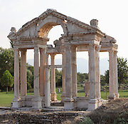 Tetrapylon or monumental gateway from the East, 2nd century AD, Aphrodisias, Aydin, Turkey. The tetrapylon greeted pilgrims visiting the Temple or Sanctuary of Aphrodite and linked the main North-South street of the town to the Sacred Way leading to a large forecourt in front of the temple. It consists of 4 rows of 4 columns and the pediment over the West columns is decorated with reliefs of Eros and Nike hunting among the acanthus leaves. Aphrodisias was a small ancient Greek city in Caria near the modern-day town of Geyre. It was named after Aphrodite, the Greek goddess of love, who had here her unique cult image, the Aphrodite of Aphrodisias. The city suffered major earthquakes in the 4th and 7th centuries which destroyed most of the ancient structures. Picture by Manuel Cohen