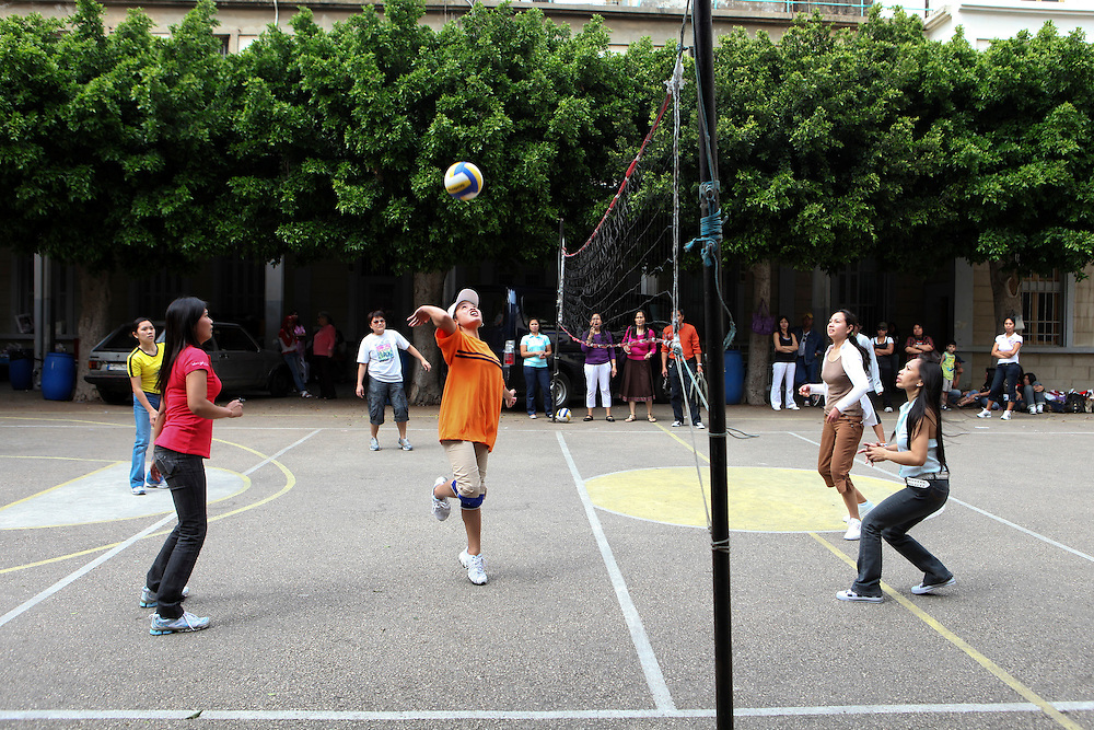 Filipino women play volleyball after church.