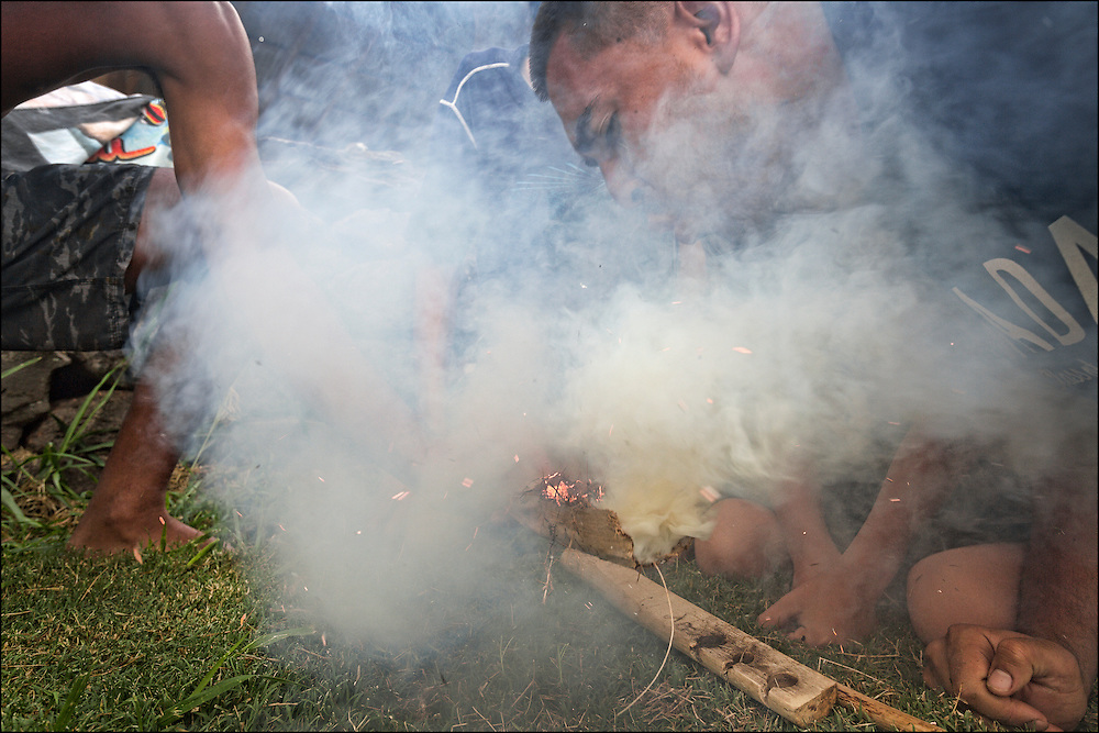 Alika Pilialoha Fonseca blows on tinder during fire making training.