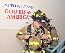 Sept. 11, 2013 - U.S. - Greg Sorber -- AFD driver Jesse Elich from Station 15, left, and Donovan Jacks from Station 1, pass a sign put up in the stairwell of the Bank of Albuquerque for the 9/11 Remembrance Stair Climb on Wedenesday, September 11, 2013. The firefighters climbed 110 floors in full bunker gear to honor the 343 firefighters who paid the ultimate sacrifice in New York on 9/11/2001. The Bank building is 22 stories so participants climbed the stairs 5 times to complete the 110 stories which is the same height as the Twin Towers. (Credit Image: © Greg Sorber/Albuquerque Journal/ZUMAPRESS.com)