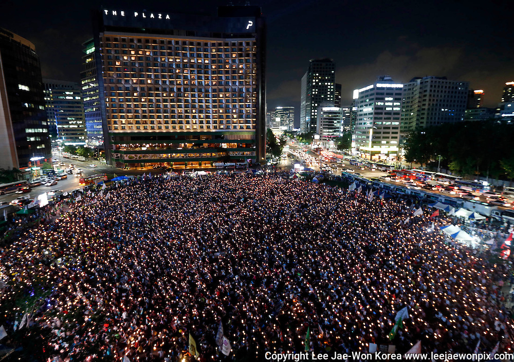 South Koreans take part in a candle-light demonstration demanding apology from South Korean President Park Geun-Hye and calling for reform of national spy agency in central Seoul August 14, 2013. /Lee Jae-Won