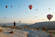 A young Australian woman backpacking in Turkey looks on at a sky full of balloons at sunrise in Göreme, Turkey.