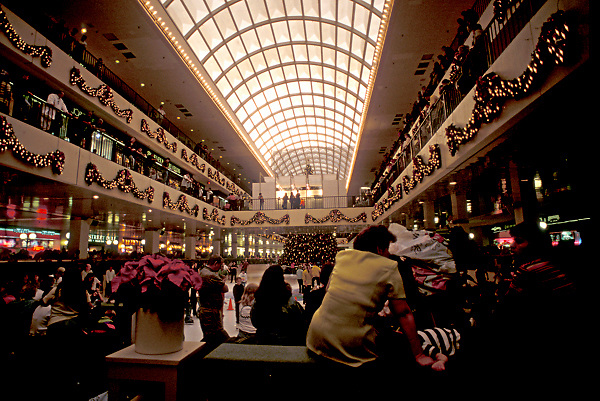 Stock photo of holiday shoppers sitting and taking a break at the Galleria skating rink in Houston Texas