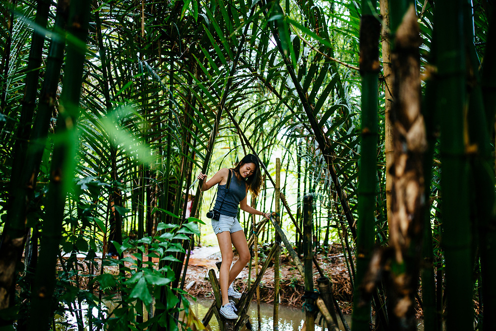 A young woman walks across a small bamboo bridge in a garden in Can Tho, in the Mekong Delta in southern Vietnam.
