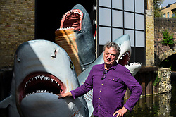 © Licensed to London News Pictures. 21/08/2020. LONDON, UK.  Architect Jaimie Shorten at the unveiling of his work SHARKS! in East London, the winner of this year's annual Antepavilion Commission.  The commission offers emerging architects, artists and makers an opportunity to create new work for temporary display.  The work comprises a group of full scale replica sharks - two Great Whites, a Tiger Shark and two Megalodon 'dinosaur' sharks - installed in the Regents Canal at Hoxton Docks, Haggerston.  Photo credit: Stephen Chung/LNP