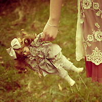 Close-up of a young girl's hand holding a vintage porcelain doll outdoors in spring