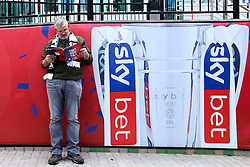 Fan stands next to a Sky Bet board outside Wembley Stadium ahead of the Sky Bet Championship Playoff Final - Mandatory by-line: Robbie Stephenson/JMP - 27/05/2019 - FOOTBALL - Wembley Stadium - London, England - Aston Villa v Derby County - Sky Bet Championship Play-off Final