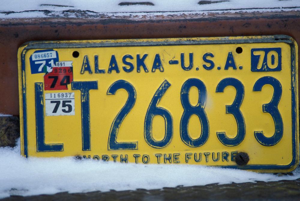 USA, Alaska, Unalakleet, Old Alaska license plate on abandoned truck on winter morning