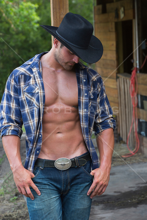 cowboy with an open shirt leaning against a wooden post in a barn