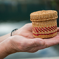 A local woman holds a basket that she wove in downtown Petersburg, a fishing village in Southeast Alaska known as Little Norway.