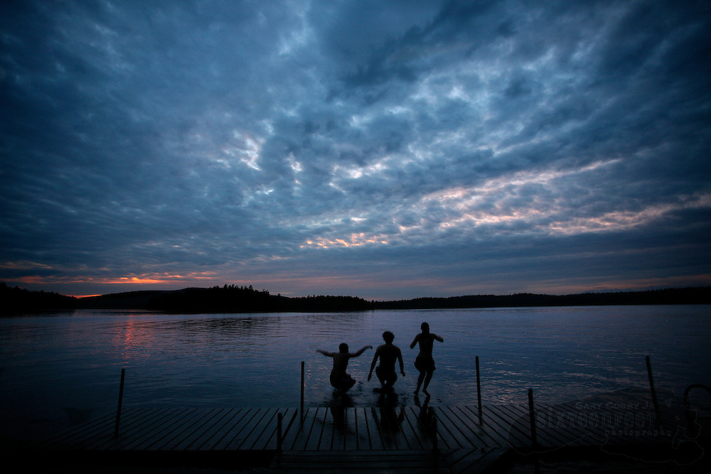 Photo by Gary Cosby Jr.  Kids jump from a dock into Tupper Lake near the town of Tupper Lake, New York in Adirondack Park just after sunset.