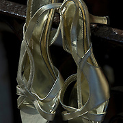 Transvestite selling his women's Merona high heeled gold metallic finish dress sandals for sales at street sale in Greenwich Village.