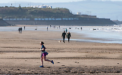 Portobello, Scotland, UK. 18 April 2020. Views of the Portobello promenade and beach on a sunny but cld and windy Saturday afternoon during the coronavirus lockdown in the UK . Iain Masterton/Alamy Live News
