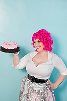 Portrait of young woman standing with hands on hips holding cake over colored background