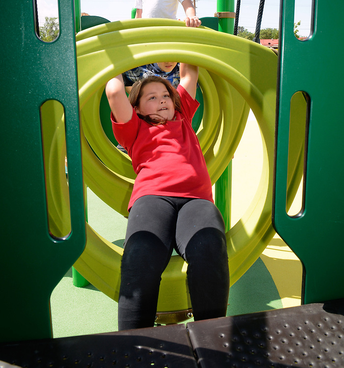 jt050917b/a sec/jim thompson/ Rosemary Benavides-9 a third grader from La Mesa Elm. plays on the playground equipment at the newly dedicated park for slain APD Officer Daniel Webster Tuesday morning. Tuesday May. 09, 2017. (Jim Thompson/Albuquerque Journal)