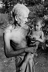 BANGLADESH DINAJPUR DISTRICT KAHAROL THANA AUG94 - A Hindu farmer holds his most recent addition to the family. In areas with little access to health, education and credit facilities, families tend to have an average of 6.5 heads...jre/Photo by Jiri Rezac..© Jiri Rezac 1994