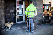 """A man and dogs are practicing """"social distancing"""" in front of a backery shop in Oberursel-Stierstadt."""