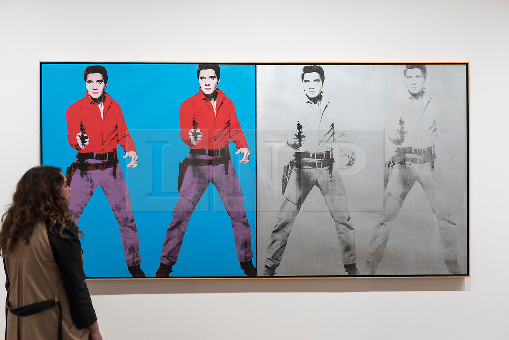 "© Licensed to London News Pictures. 10/03/2020. LONDON, UK. A staff member poses next to ""Elvis I and II"", 1963-4, by Andy Warhol. Preview of ""Andy Warhol"", a retrospective of over 100 works by one of the most recognisable artists of the late 20th century.  The exhibition runs 12 March to 6 September 2020 at Tate Modern.  Photo credit: Stephen Chung/LNP"