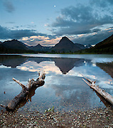 "Dawn light illuminates Pray Lake and Sinopah Mountain (8271 feet or 2521 meters) in Glacier National Park, Montana, USA. Since 1932, Canada and USA have shared Waterton-Glacier International Peace Park, which UNESCO declared a World Heritage Site (1995) containing two Biosphere Reserves (1976). Rocks in the park are primarily sedimentary layers deposited in shallow seas over 1.6 billion to 800 million years ago. During the tectonic formation of the Rocky Mountains 170 million years ago, the Lewis Overthrust displaced these old rocks over newer Cretaceous age rocks. Glaciers carved spectacular U-shaped valleys and pyramidal peaks as recently as the Last Glacial Maximum (the last ""Ice Age"" 25,000 to 13,000 years ago). Of the 150 glaciers existing in the mid 1800s, only 25 active glaciers remain in the park as of 2010, and all may disappear by 2020, say climate scientists. (Panorama stitched from 3 images.)"