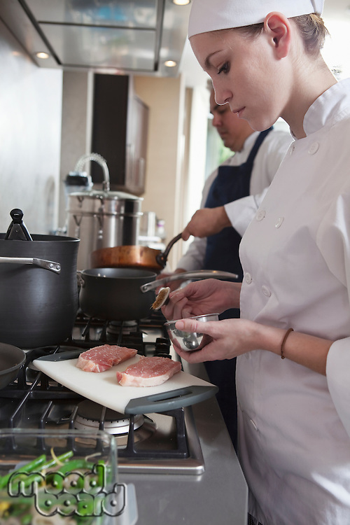 Young chef preparing raw meat