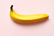 Close up of a ripe banana isolated on pink background.