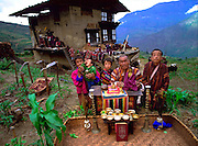 Nalim and Namgay's family of Bhutan, with all of their possessions. From pages 72-73, Material World. The family of subsistence farmers lives in a 3-story rammed-earth house in the hillside village of Shingkhey, Bhutan. Namgay, who has a hunched back and a clubfoot, grinds grain for neighbors with a small mill his family purchased from the government. They are paying for the mill as they can (often the payment is made in grain and mustard oil). Namgay is also a reader of sacred texts and conducts house cleansing and healing ceremonies for their 14-house village.