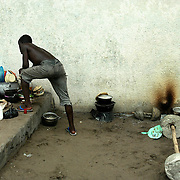 Child preparing the meal in the prison ground, Cotonou, Benin september 2003 - The prison of Cotonou has a part reserved for the young criminals. Many of these young criminals are street children who consume drugs.  They have been put in prison for the use, possession and/or trade of drug; and also often for violence and rape. Visiting room.