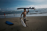 BALI, INDONESIA; April 20, 2015: A surf instructor carries surf boards after teaching tourist for surfing in Batubolong beach, Bali, Indonesia on Monday, April 20, 2015.