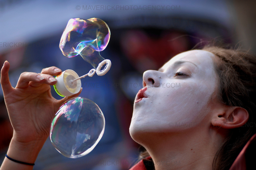 "Standalone Picture.  An actress blows bubbles on Edinburgh's Royal Mile.  The actress is playing the character ""The Red Queen"" in a musical adaptation of Lewis Carroll's ""Through the Looking Glass"" which is on during the Edinburgh Festival."