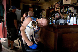 "03 Sept  2005. New Orleans, Louisiana. Post hurricane Katrina.<br /> Johnny White's Sports Bar on Bourbon Street in the French Quarter - with it's claim to ""Never Close."" The bar has remained open throughout.  John Webster gives his dog Muffin a drink at the bar.<br /> Photo Credit ©: Charlie Varley/varleypix.com"