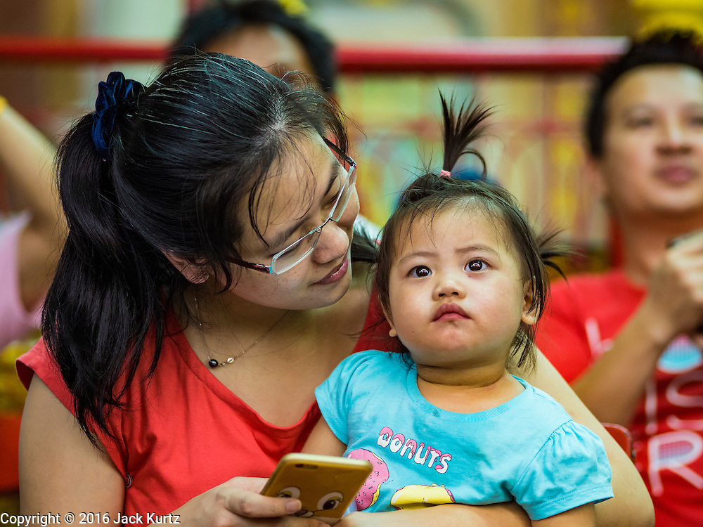 04 OCTOBER 2016 - BANGKOK, THAILAND:  A woman and her daughter watch the Chinese opera at the Vegetarian Festival at the Chit Sia Ma Chinese shrine in Bangkok. The Vegetarian Festival is celebrated throughout Thailand. It is the Thai version of the The Nine Emperor Gods Festival, a nine-day Taoist celebration beginning on the eve of 9th lunar month of the Chinese calendar. During a period of nine days, those who are participating in the festival dress all in white and abstain from eating meat, poultry, seafood, and dairy products. Vendors and proprietors of restaurants indicate that vegetarian food is for sale by putting a yellow flag out with Thai characters for meatless written on it in red.    PHOTO BY JACK KURTZ