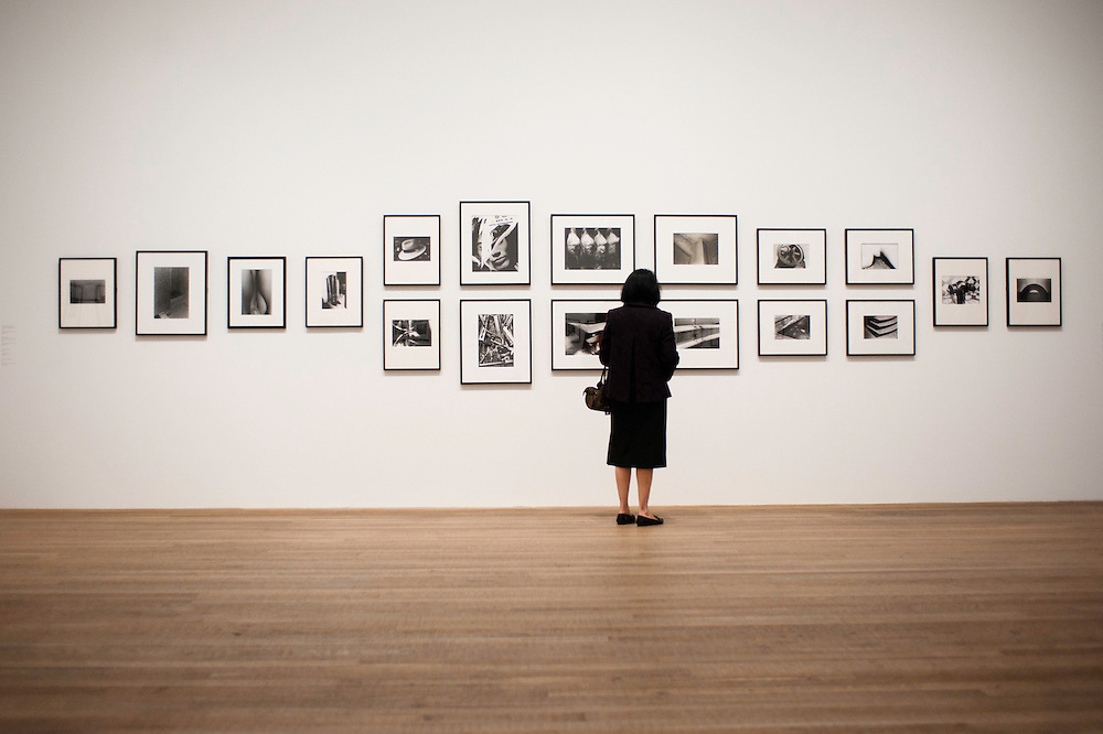 London, UK - 8 October 2012: a visitor looks up at pictures by Daido Moriyama. The exhibition examine the relationship between the work of William Klein (b.1928) and that of Daido Moriyama (b.1938). Taking as its central theme the cities of New York and Tokyo, the show explores both artists' celebrated depictions of modern urban life.