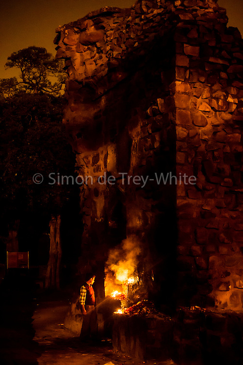 18th December 2014, New Delhi, India. A man stands by as candles burn in a niche amid the ruins of Feroz Shah Kotla left by believers who prayed and made offerings and asked for wishes to be granted by Djinns in the ruins of Feroz Shah Kotla in New Delhi, India on the 18th December 2014<br /> <br /> PHOTOGRAPH BY AND COPYRIGHT OF SIMON DE TREY-WHITE a photographer in delhi<br /> + 91 98103 99809. Email: simon@simondetreywhite.com<br /> <br /> People have been coming to Firoz Shah Kotla to leave written notes and offerings for Djinns in the hopes of getting wishes granted since the late 1970's. Jinn, jann or djinn are supernatural creatures in Islamic mythology as well as pre-Islamic Arabian mythology. They are mentioned frequently in the Quran  and other Islamic texts and inhabit an unseen world called Djinnestan. In Islamic theology jinn are said to be creatures with free will, made from smokeless fire by Allah as humans were made of clay, among other things. According to the Quran, jinn have free will, and Iblis abused this freedom in front of Allah by refusing to bow to Adam when Allah ordered angels and jinn to do so. For disobeying Allah, Iblis was expelled from Paradise and called &quot;Shaytan&quot; (Satan).They are usually invisible to humans, but humans do appear clearly to jinn, as they can possess them. Like humans, jinn will also be judged on the Day of Judgment and will be sent to Paradise or Hell according to their deeds. Feroz Shah Tughlaq (r. 1351&ndash;88), the Sultan of Delhi, established the fortified city of Ferozabad in 1354, as the new capital of the Delhi Sultanate, and included in it the site of the present Feroz Shah Kotla. Kotla literally means fortress or citadel.